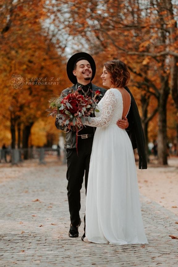 Portrait d'un couple de mariés contemporain - magnifique robe blanche de mariée en dentelle et marié portant un chapeau noir