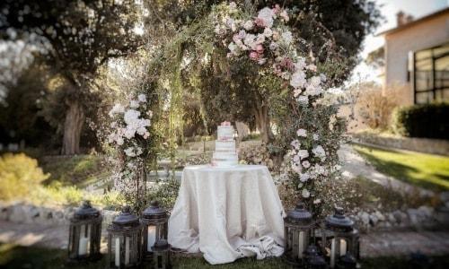 Mise en scène d'une pièce montée pour un un mariage romantique, chic et de prestige sous une arche fleurie