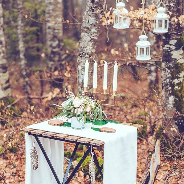 Décoration champêtre et automnale pour un mariage en forêt - lanterne, bougies, drapé blanc -